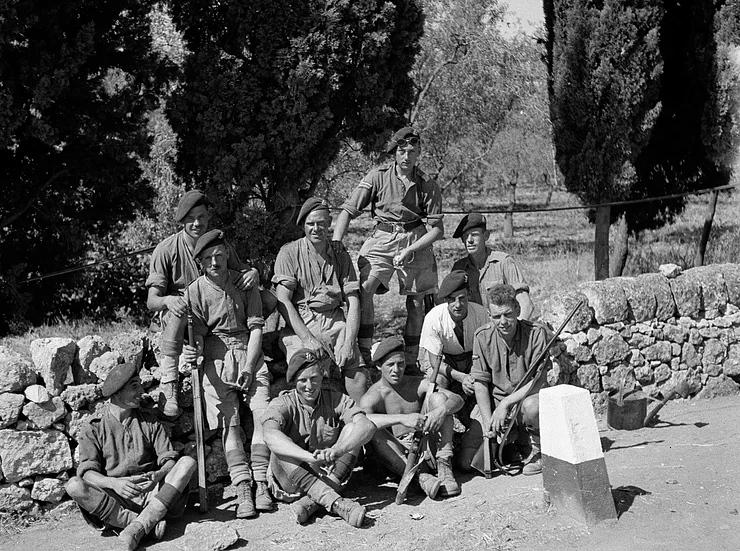 A black and white picture with a group of ten young men sitting in front of a brick wall on a road. They are all in uniform, and most are grinning. Some are sitting cross legged on the road at the front and looking rather hot in the sun. It looks like they have just been told a joke, as one of them is turning his head to laugh.