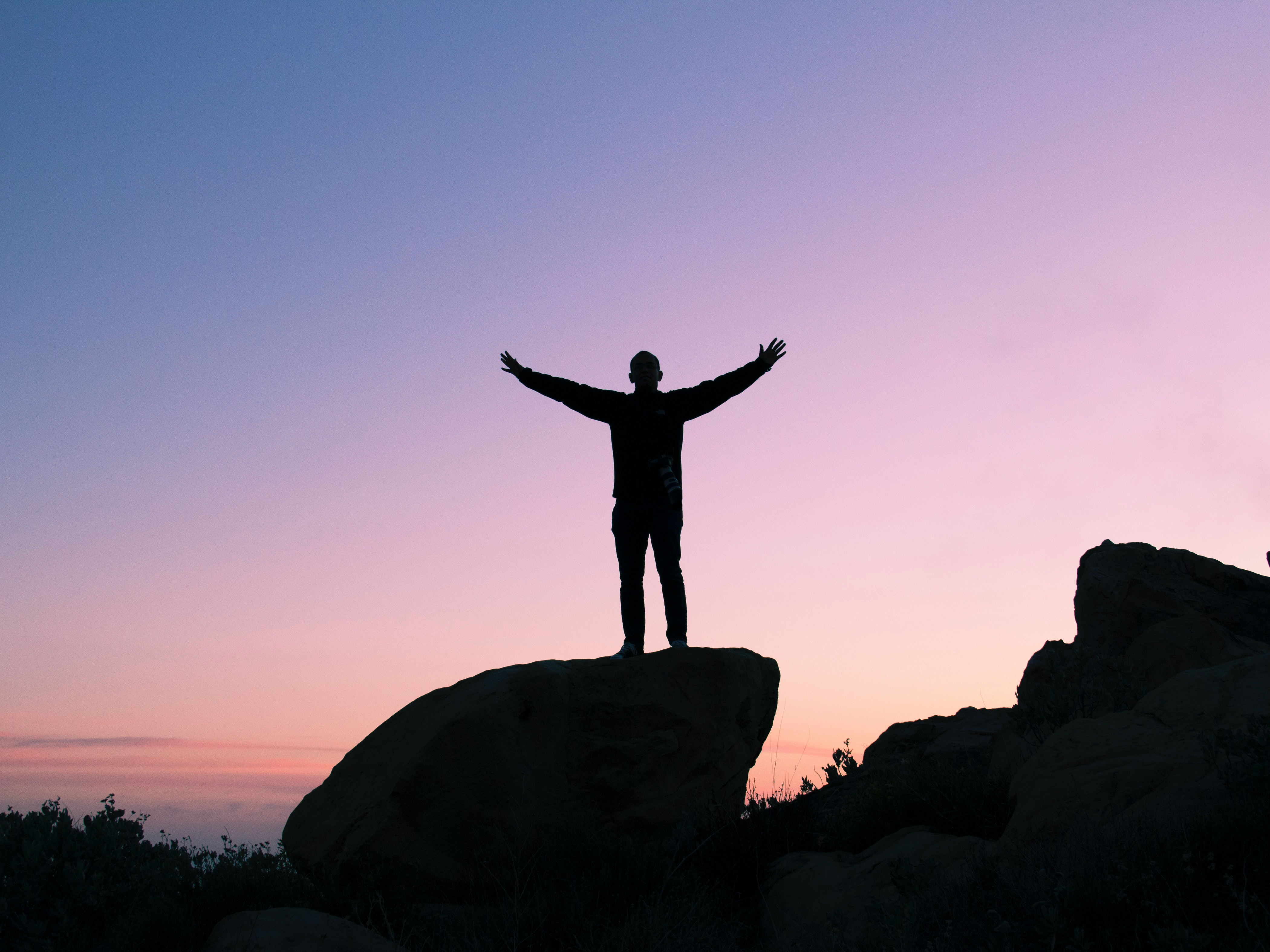 A man stands on a rock with arms outstretched, silhouetted against a sunrise